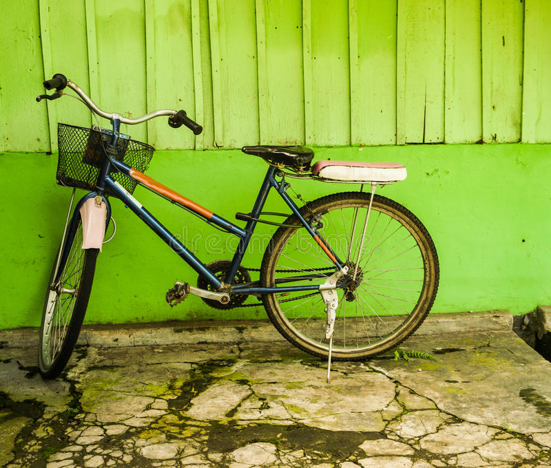 An old bicycle parked near green wall photo taken in Semarang Indonesia. Java stock images