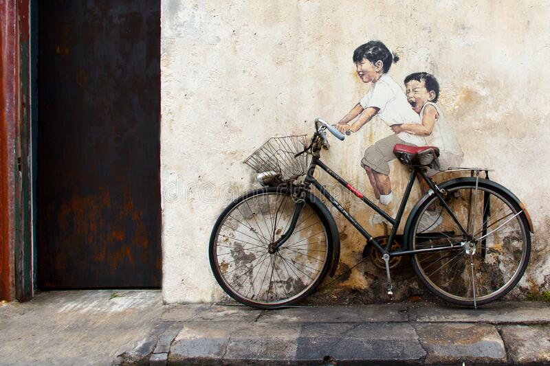 Sibling cyclist, Street Art at George Town. Old bicycle recycled in a bicycle mural street art at Armenian Street, George Town, Penang, by Lithuanian artist royalty free stock photo