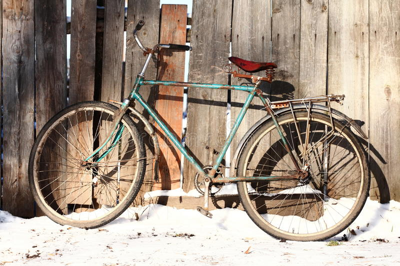 Old bicycle. Old rusty bicycle leaning against wooden fence stock images