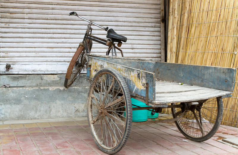 Old bicycle with trailer in Delhi, India. In front of a closed shop royalty free stock images