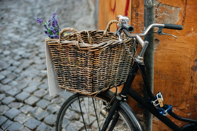 Old bicycle with wooden basket and flowers on the city street near orange wall. Old black bicycle with brown wooden basket and blue flowers on the city street royalty free stock images