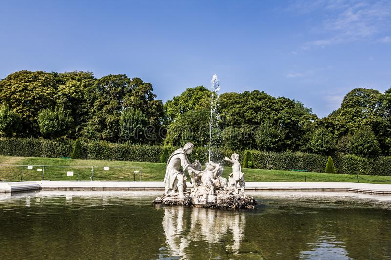 old big baroque fountain made of white marble. Beautiful fountain with antique sculptures in the park royalty free stock image