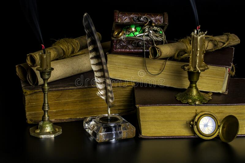 Old books, smoldering candles, documents in scrolls, a treasure chest on a black background. Old big books, smoldering candles in bronze candlesticks, documents royalty free stock image