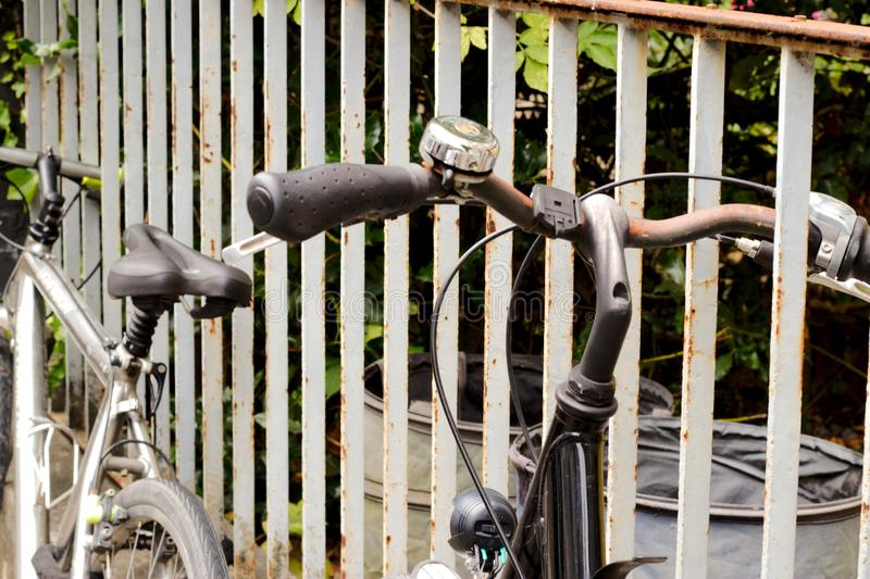 old bike leaning on a fence stock photo