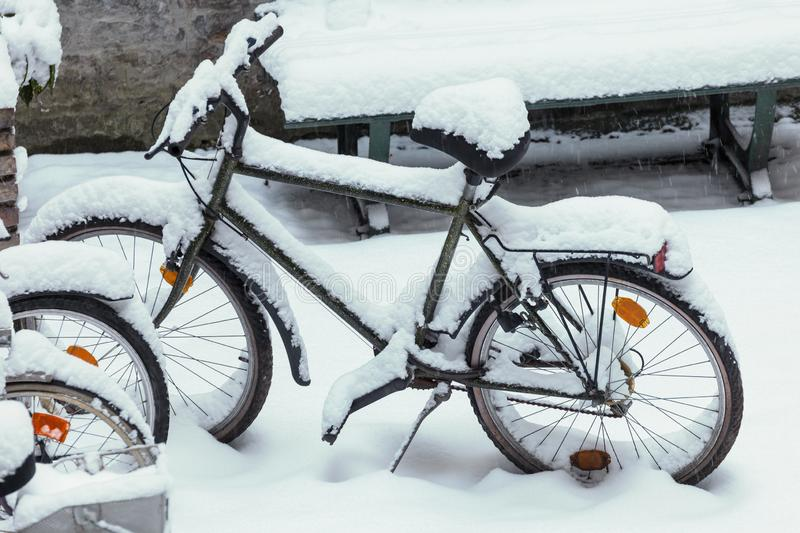 Old bike standing outdoors in the snow. Winter time, transportation and weather concept royalty free stock images