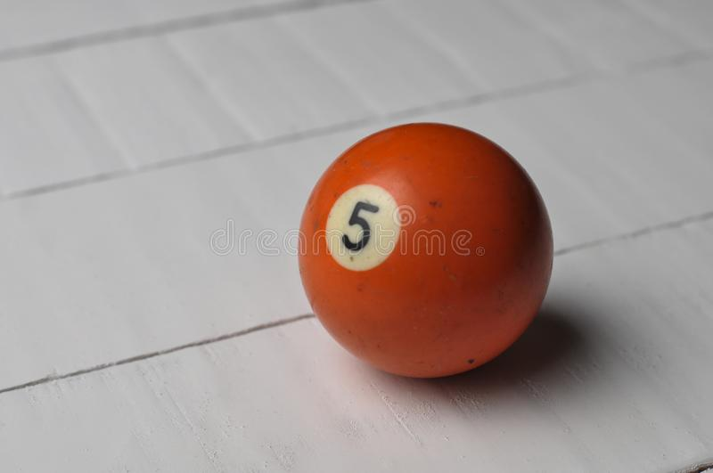 Old billiard ball number 5 orange color on white wooden table background, copy space. Old billiard ball number 5  orange color  on white wooden table background stock photos