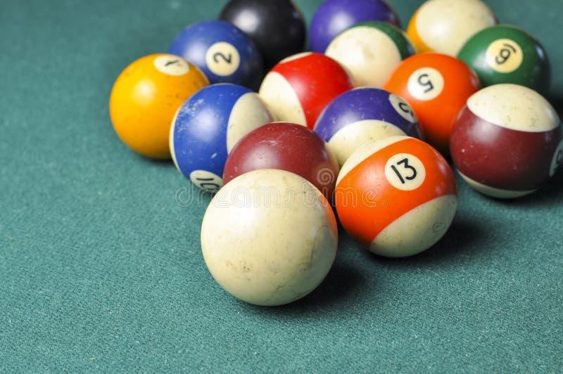 Old billiard balls composition on green pool table stock photos