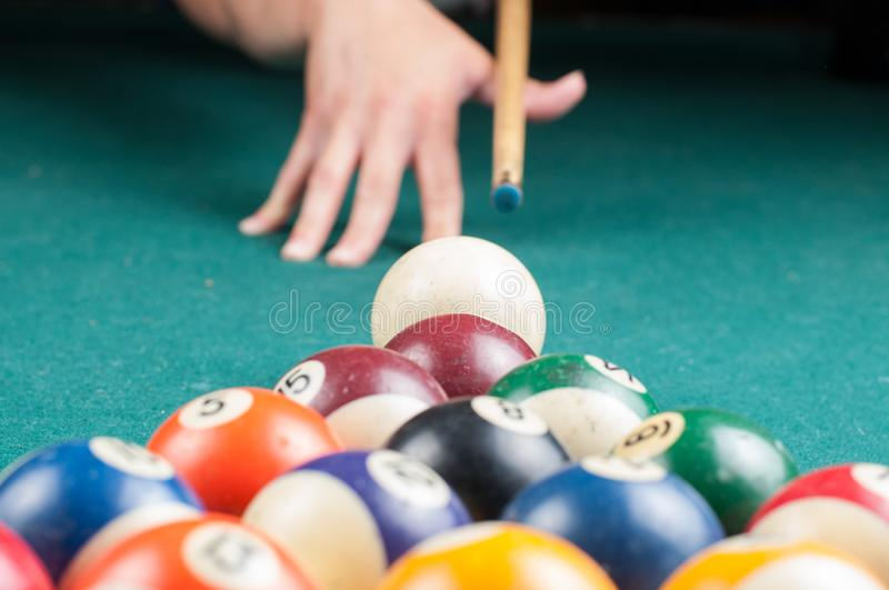 Old billiard balls and stick on a green table. billiard balls isolated on a green background stock photos