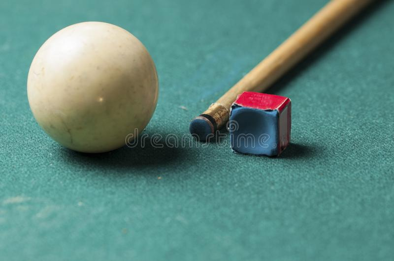 Old billiard white ball and stick on a green table. billiard balls isolated on a green background. Old billiard white ball and stick  on a green table. billiard royalty free stock image