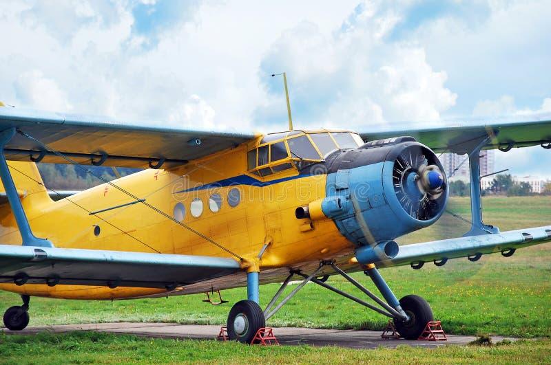Old biplane. Against blue sky stock photos
