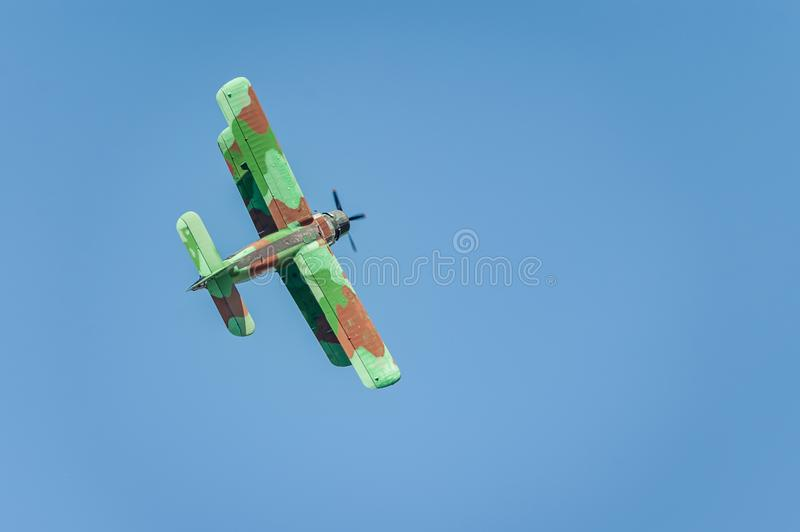 Old biplane aircraft flies and shows a performance at the airshow in the clear blue sky. Tukums, Latvia, July 20, 2019: Airshow `Wings over Baltics Airshow 2019 royalty free stock photos