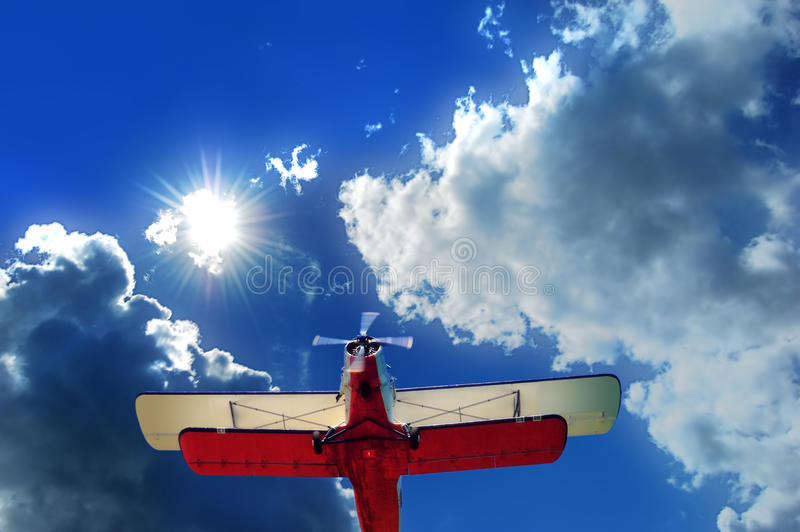 Old biplane in the sky. A Biplane in the sky with clounds and a bright sun in the background royalty free stock photos