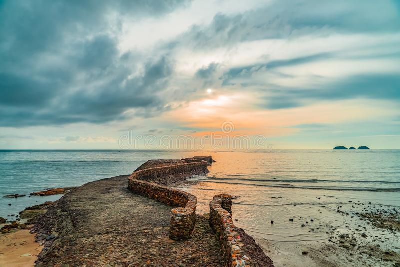 Old birck rock jetty near coastline at sunset.  stock photo