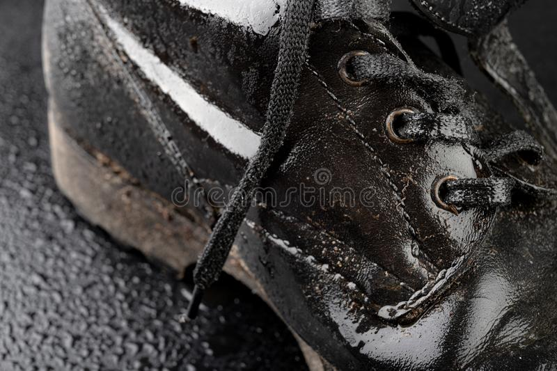 Old black army boots wet from the rain. Footwear resistant to difficult terrain conditions. Dark background art autumn casual classic closeup clothing dirty royalty free stock images