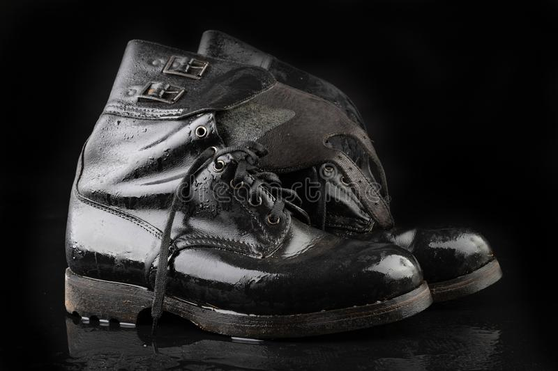 Old black army boots wet from the rain. Footwear resistant to difficult terrain conditions. Dark background art autumn casual classic closeup clothing dirty stock photography
