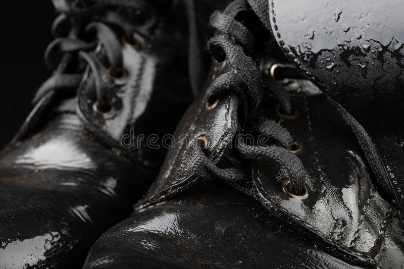 Old black army boots wet from the rain. Footwear resistant to difficult terrain conditions. Dark background art autumn casual classic closeup clothing dirty royalty free stock photography