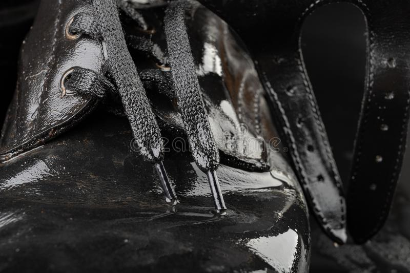 Old black army boots wet from the rain. Footwear resistant to difficult terrain conditions. Dark background art autumn casual classic closeup clothing dirty royalty free stock image