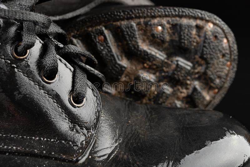 Old black army boots wet from the rain. Footwear resistant to difficult terrain conditions. Dark background art autumn casual classic closeup clothing dirty stock photos