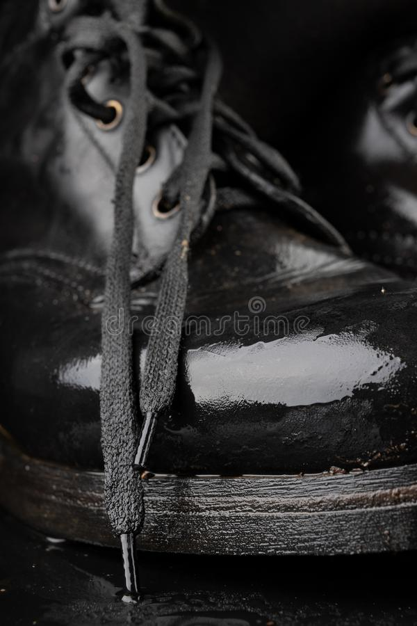Old black army boots wet from the rain. Footwear resistant to difficult terrain conditions. Dark background art autumn casual classic closeup clothing dirty stock image