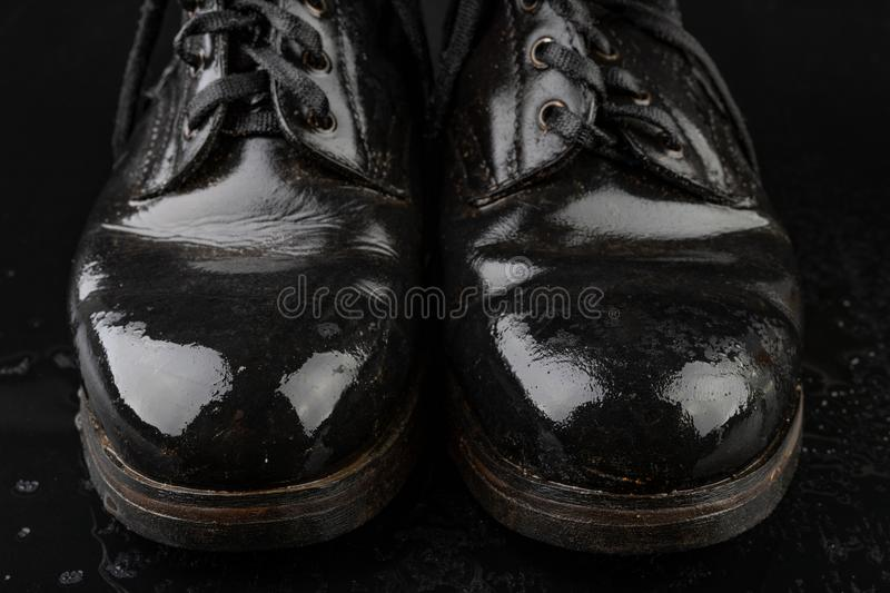 Old black army boots wet from the rain. Footwear resistant to difficult terrain conditions. Dark background art autumn casual classic closeup clothing dirty stock photo