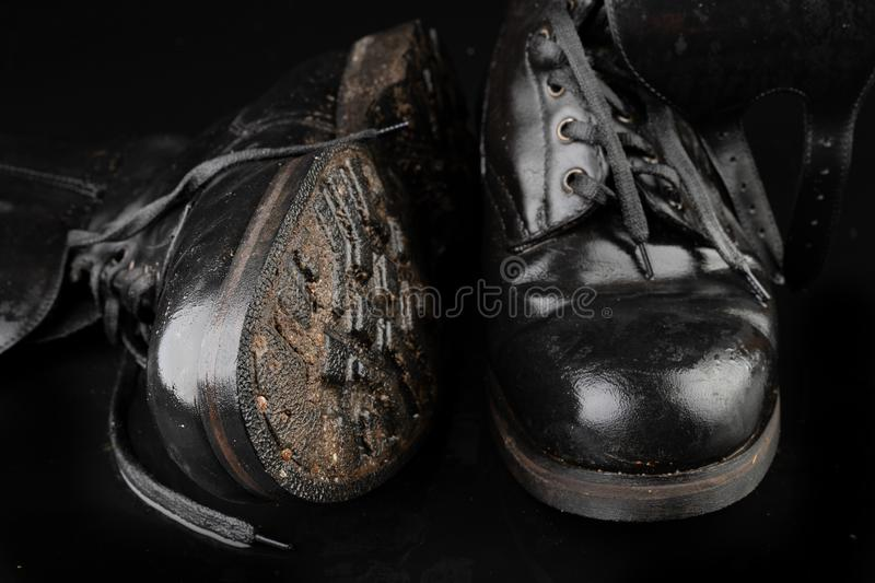 Old black army boots wet from the rain. Footwear resistant to difficult terrain conditions. Dark background art autumn casual classic closeup clothing dirty royalty free stock photo