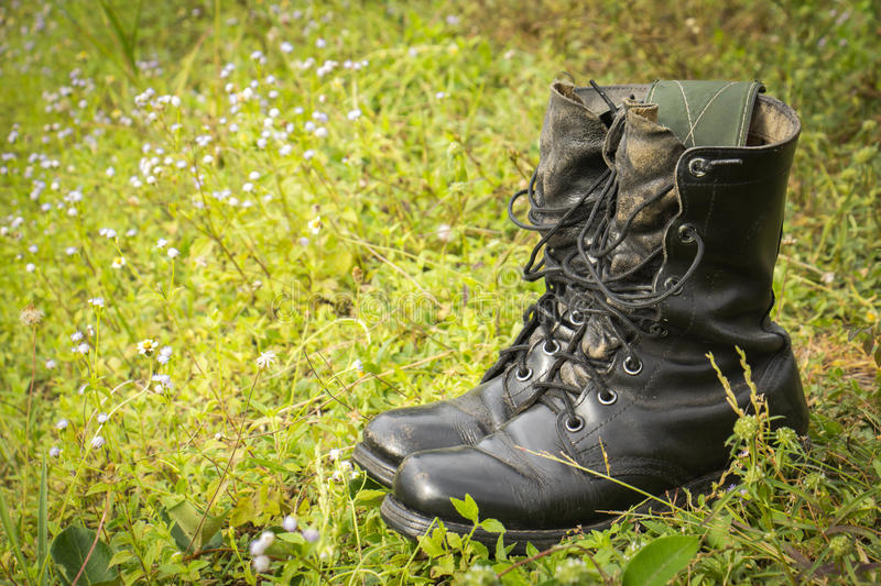 Old black combat boots on grass.selective focus.soft focus the f royalty free stock photography