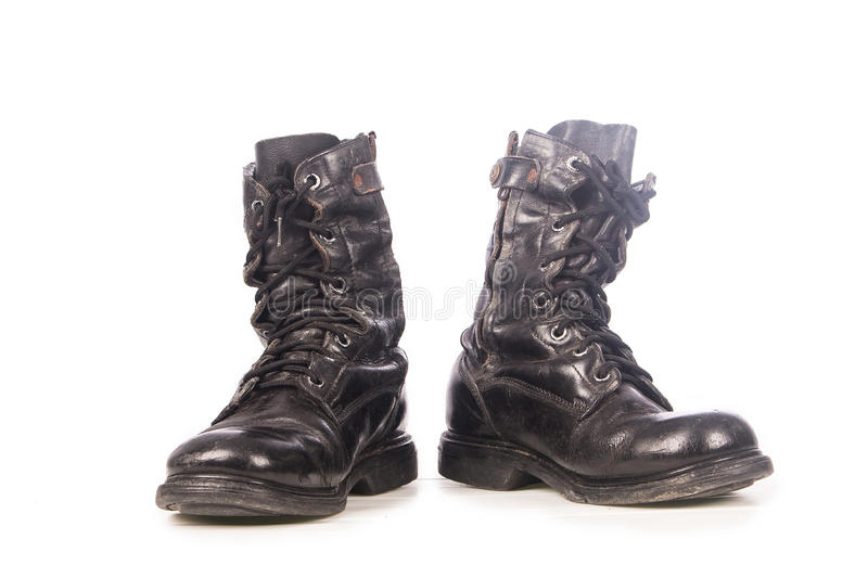 Old black combat boots. On white background royalty free stock photography