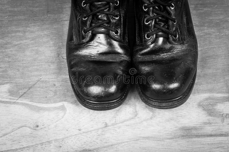 Old black combat boots. On wooden background royalty free stock image