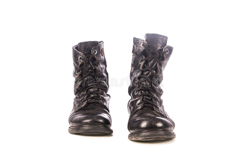 Old black combat boots. On wooden background royalty free stock photos