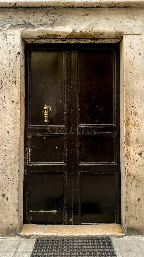 Old black door with bronze pull handle. Black door with bronze pull handle royalty free stock photo