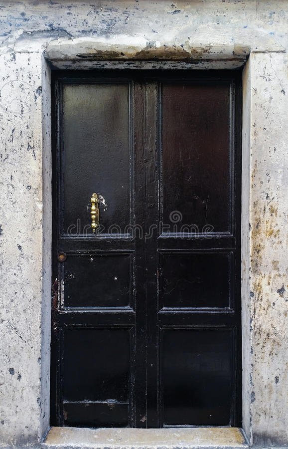 Old black door with bronze pull handle. Close up of an old black exterior door with bronze pull handle royalty free stock images