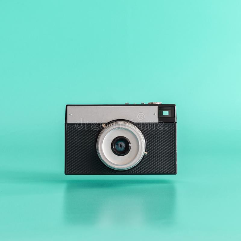 Old black film camera levitating on blue background.  Minimal concept stock photo
