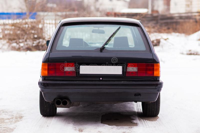 Old, black, German family car rear view in winter.  stock photography