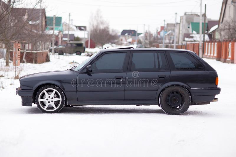 Old, black, German family car side view in winter.  royalty free stock images