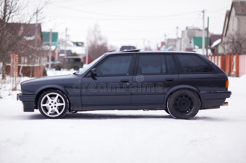 Old, black, German family car side view in winter.  royalty free stock photo