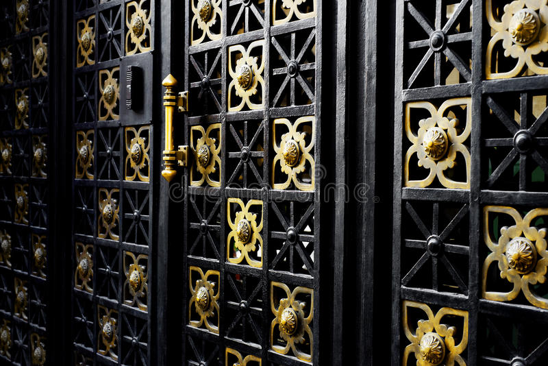 Old black iron gate with golden ornaments royalty free stock image