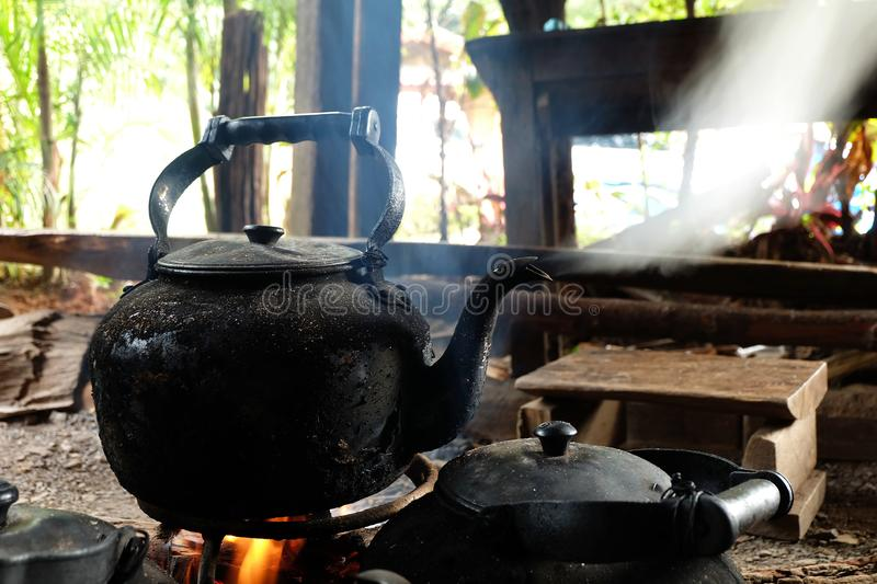 Old black kettle boiling on charcoal stove stock photo