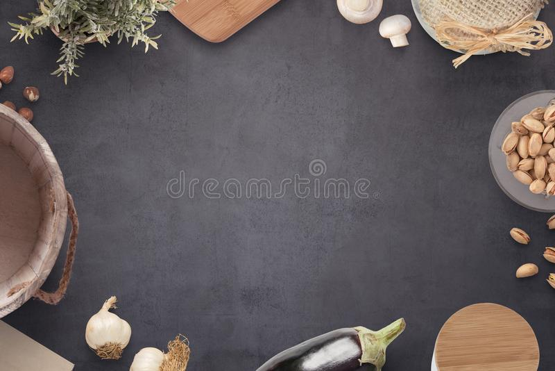 Old black kitchen table with cooking ingredients, milk bucket, cutting board, jam jar, spices box and plant royalty free stock photos