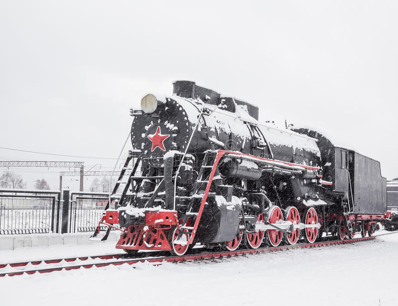Old black locomotive. The old black locomotive is parked in the snow stock image