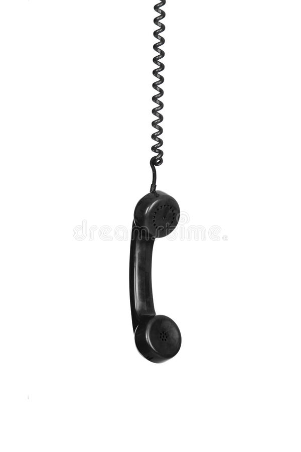 Old black phone hanging of a cable royalty free stock images