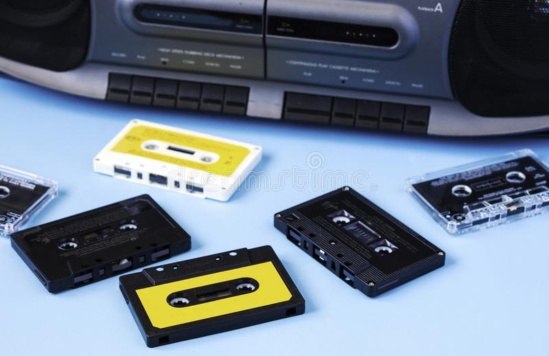 Old black retro cassette music audio tape recorder and retro cassette tape collection on blue background stock photo