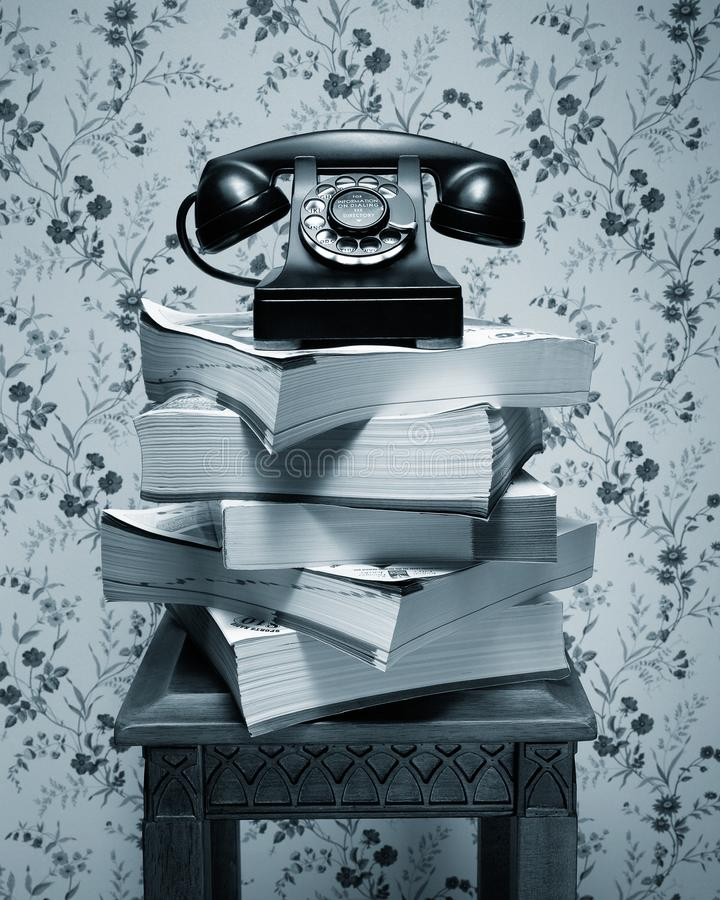 Old black rotary dial telephone on stack of phone books. Vintage antique black rotary dial telephone standing on stack of phone books and wooden table stock images