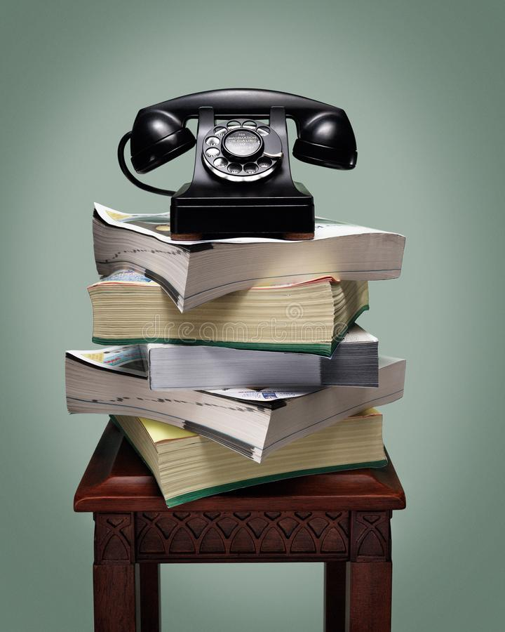 Old black rotary dial telephone on stack of phone books. Vintage antique black rotary dial telephone standing on stack of phone books and wooden table stock photo