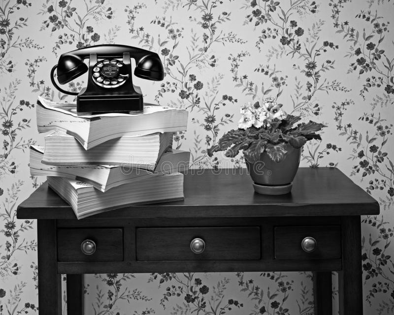 Old black rotary dial telephone on stack of phone books. Vintage antique black rotary dial telephone standing on stack of phone books and wooden table with plant royalty free stock photos