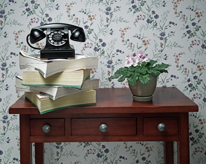 Old black rotary dial telephone on stack of phone books. Vintage antique black rotary dial telephone standing on stack of phone books and wooden table with plant royalty free stock photo