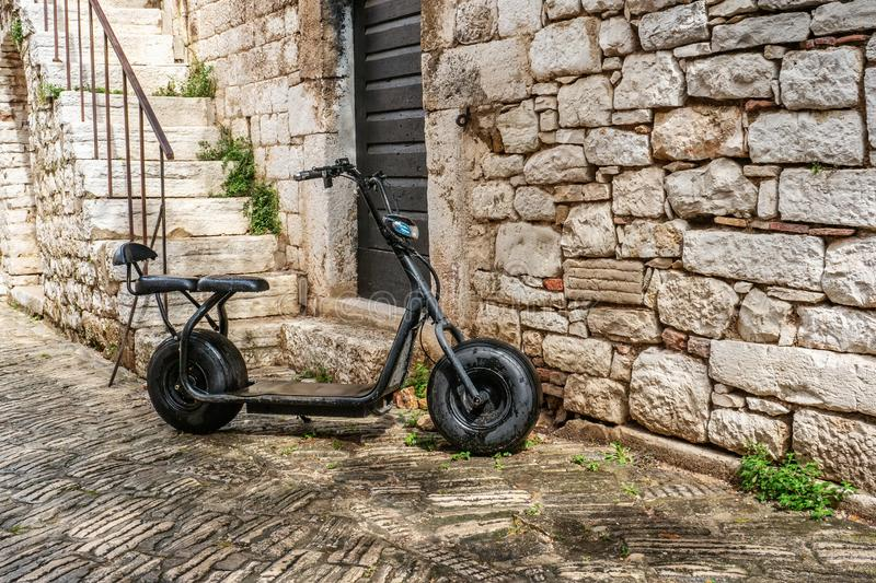 An old black Scooter is parked on the street by the stone wall. Urban eco-friendly transport.  royalty free stock photo