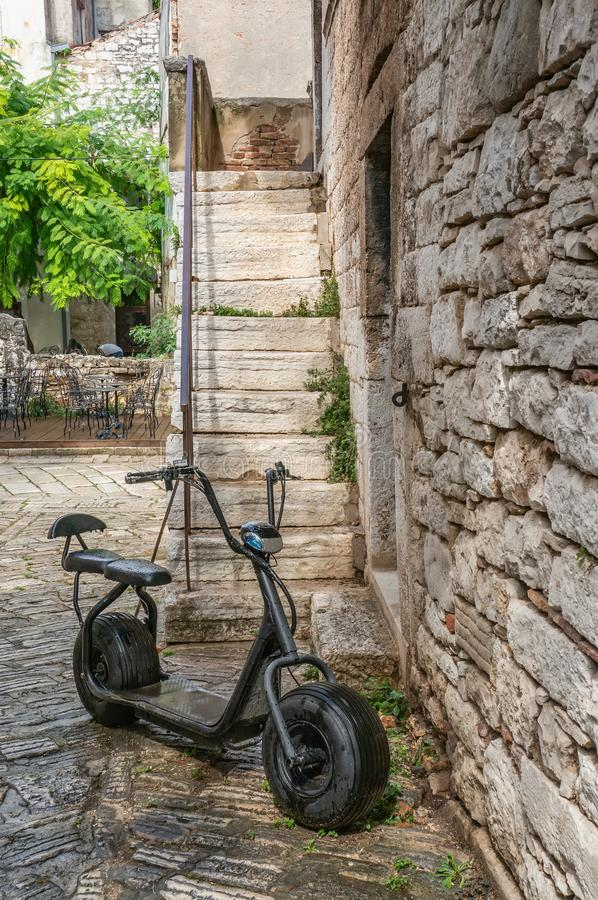 An old black Scooter is parked on the street by the stone wall. Urban eco-friendly transport.  stock photo
