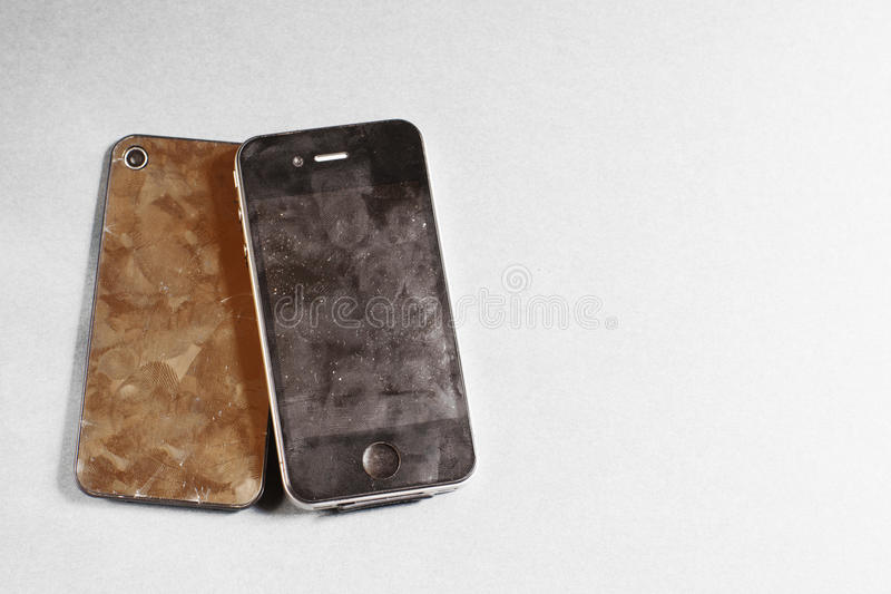Old black smartphone on gray background. Shabby,frayed disassembled mobile phone, free space for commercials royalty free stock photo