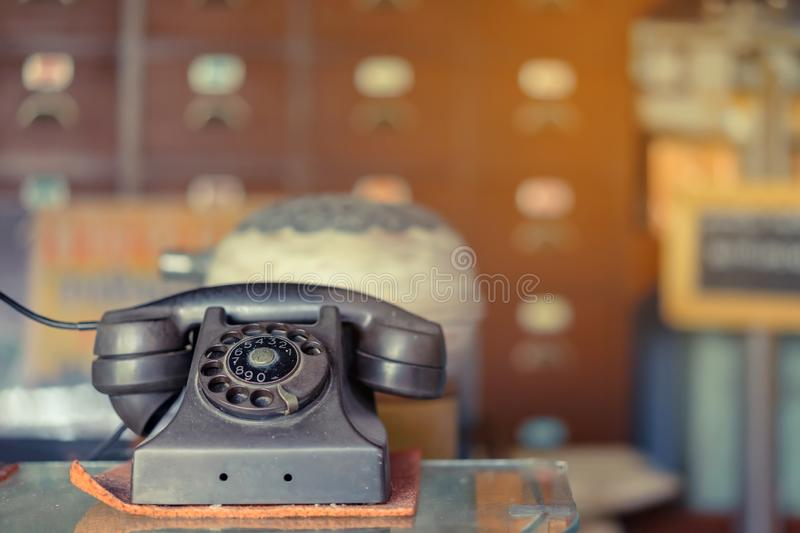 The old black telephone with rotary dial with dust and scratches placed on a clear glass cabinet stock photography