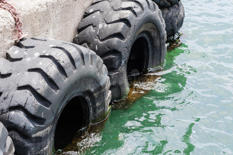 Old black tires used as bumpers at dock royalty free stock photos